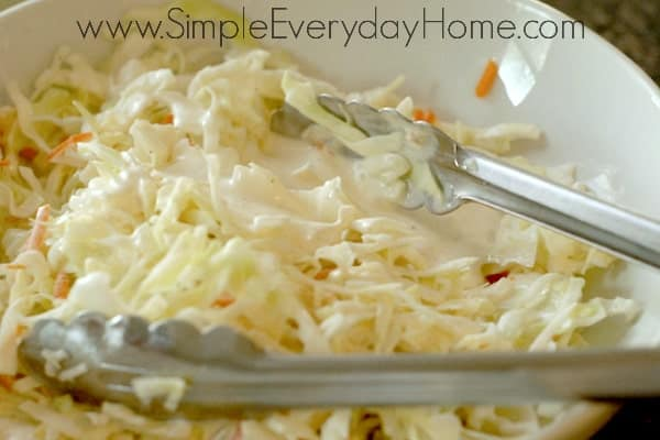 Slaw being mixed with tongs