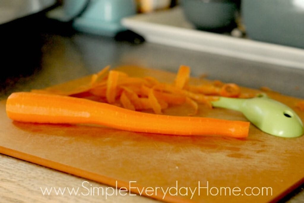 Peeled carrot on a cutting board with green peeler