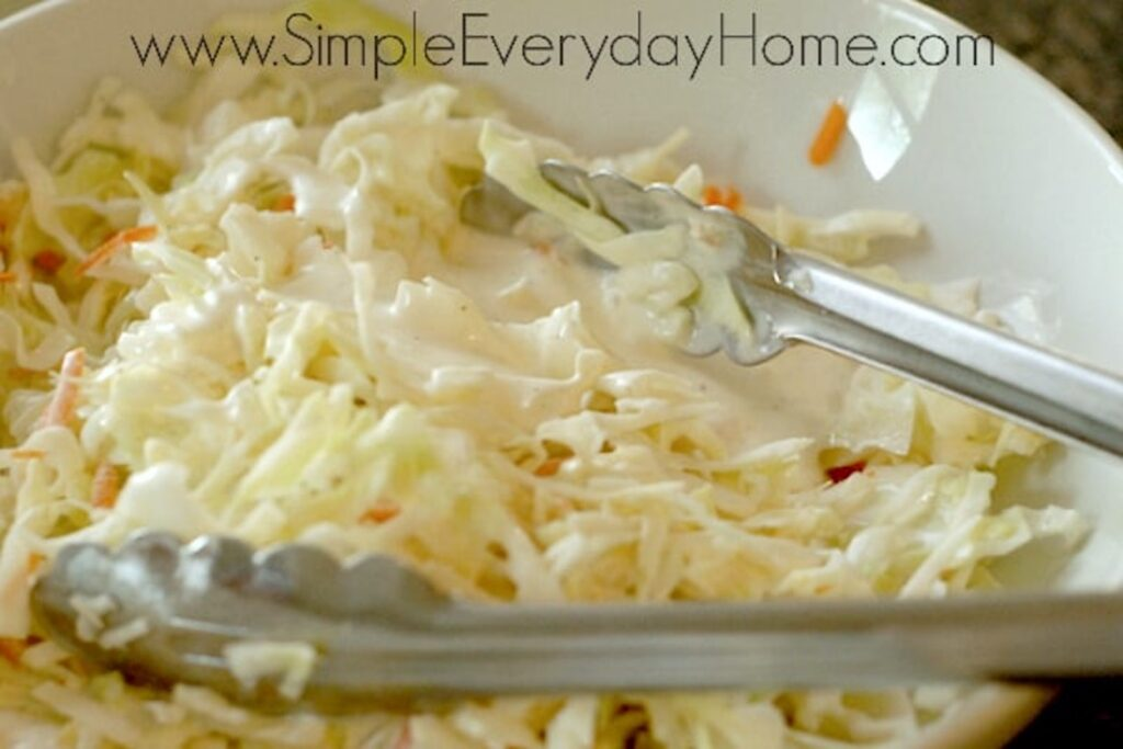 Cole slaw being mixed with dressing with metal tongs