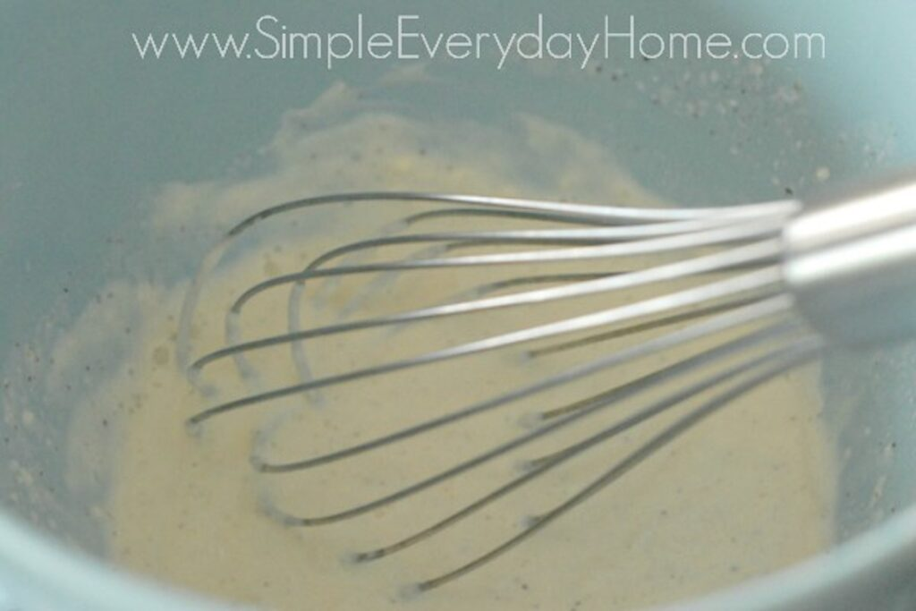 Mayo and milk being whisked in blue bowl