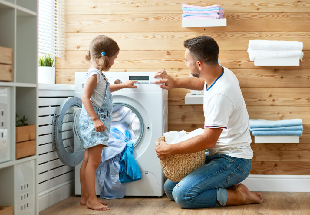 A man and his daughter putting laundry in a washer