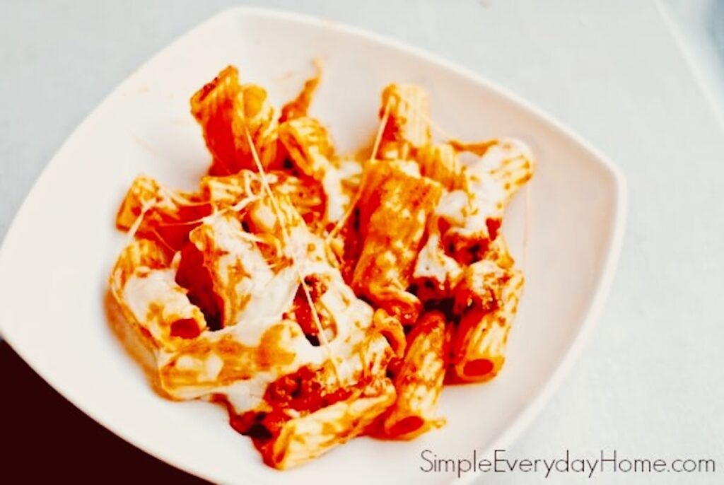 Finished rigatoni and melted cheese in bowl