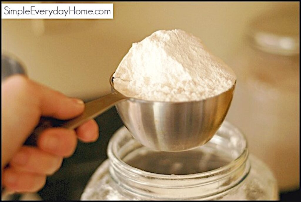 Flour being scooped out of a jar with a measuring cup