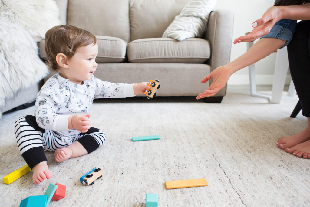 A baby sitting on the floor playing with wooden trains and handing a piece to his mother
