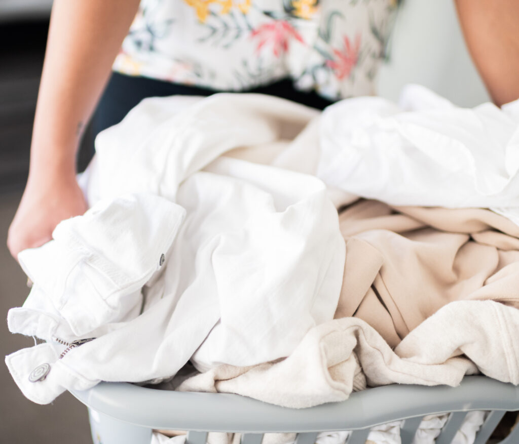 Woman holding a laundry basket overflowing with laundry