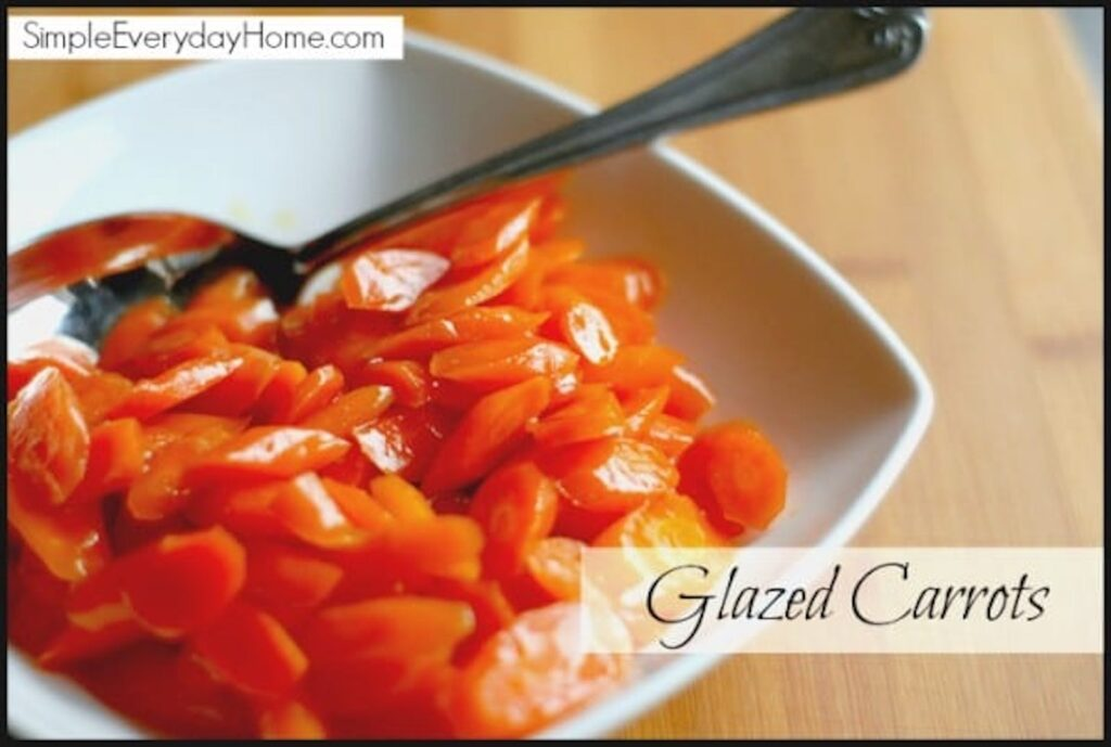 Glazed carrots in white dish with serving spoon